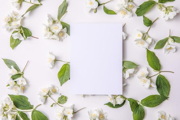 Composizione di foglie verdi e fiori di gelsomino con un foglio bianco per il testo su un grigio