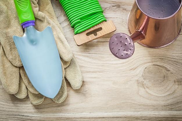Composizione della mano vanga guanti annaffiatoio giardino cravatta morbida sul concetto di agricoltura del bordo di legno