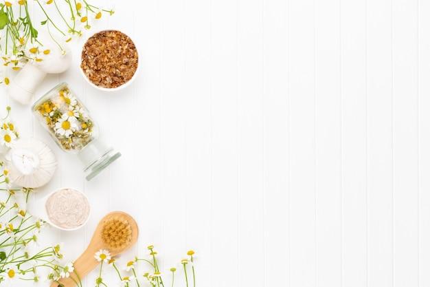 Composizione cosmetica fatta in casa, aromaterapia con cosmetici naturali e fiori di camomilla su sfondo chiaro.