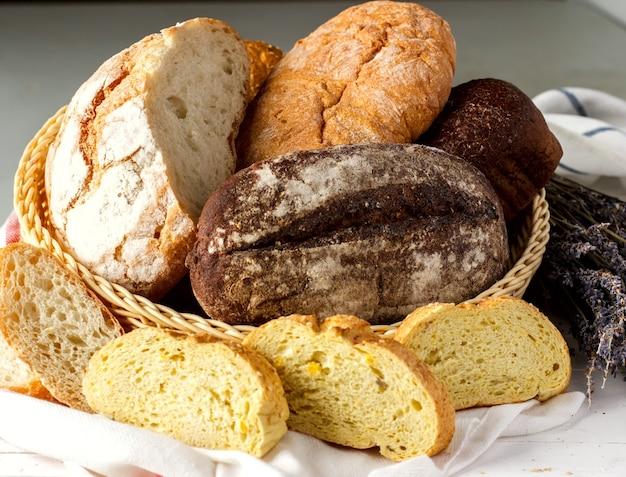 Composizione di pane bianco e nero fatto in casa in un cesto di vimini