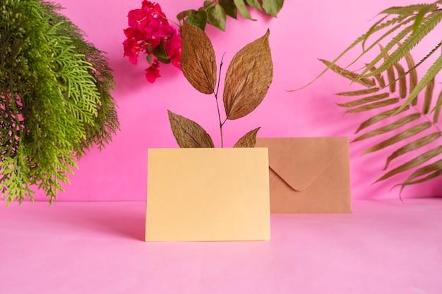 Concetto di idee di composizione con prodotti. biglietto di auguri su sfondo rosa decorato con foglie secche, foglie di pino e fiori rossi