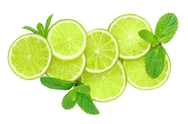 Composizione di fette di lime isolato e foglie di menta con tracciato di ritaglio.