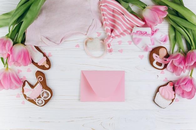 Composizione per neonati su uno sfondo in legno con busta, vestiti e biscotti