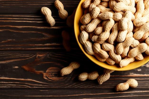 Composizione di arachidi che servono per fare l'olio, burro di arachidi. ottimo per un'alimentazione sana e dietetica. concetto di: condimenti, frutta secca, cibo. posto per il testo. vista dall'alto.