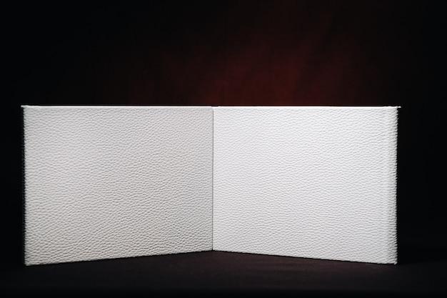 Composizione di fotolibri in pelle bianca naturale di diverse dimensioni. il libro bianco su uno sfondo scuro.