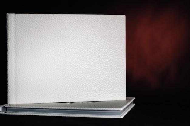 Composizione di fotolibri in pelle bianca naturale di diverse dimensioni. il libro bianco su sfondo scuro.