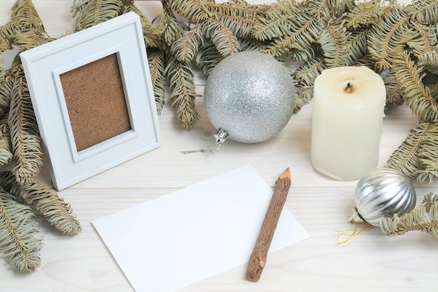 Composizione di una cornice per foto, carta, matita su un tema natalizio su una superficie di legno bianca