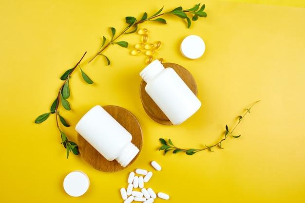 Composizione di pillole, olio di pesce, vitamine con foglie verdi sulla superficie gialla