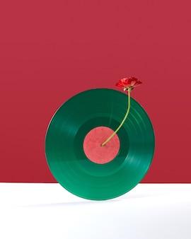 Composizione di un fiore rosso che decora un disco audio in vinile su un doppio sfondo rosso bianco con spazio di copia