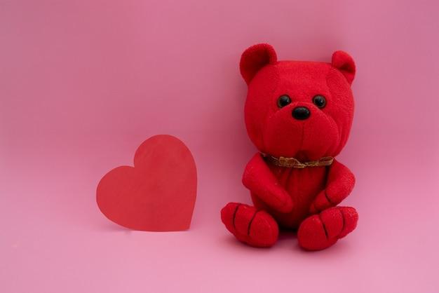 Composizione rosso orso e cuore del giocattolo su una rosa