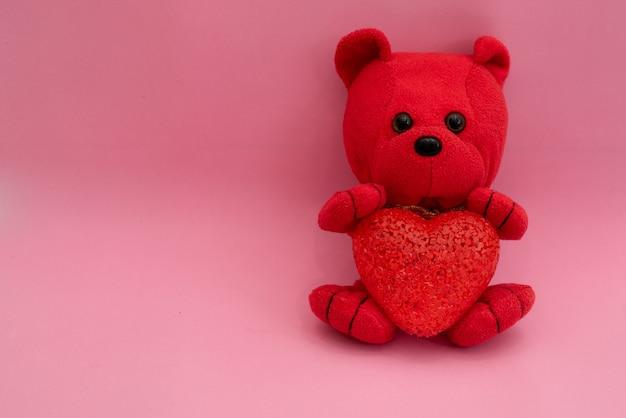 Composizione rosso orsetto giocattolo con un cuore nelle zampe su una rosa.