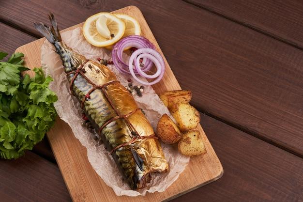 Composizione pesce sgombro affumicato con patate guarnite cipolle verdi al limone servite su tavola di legno vista dall'alto