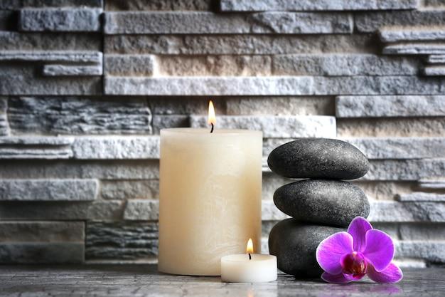 Composizione di ciottoli spa, fiori e candele sul muro di mattoni grigi
