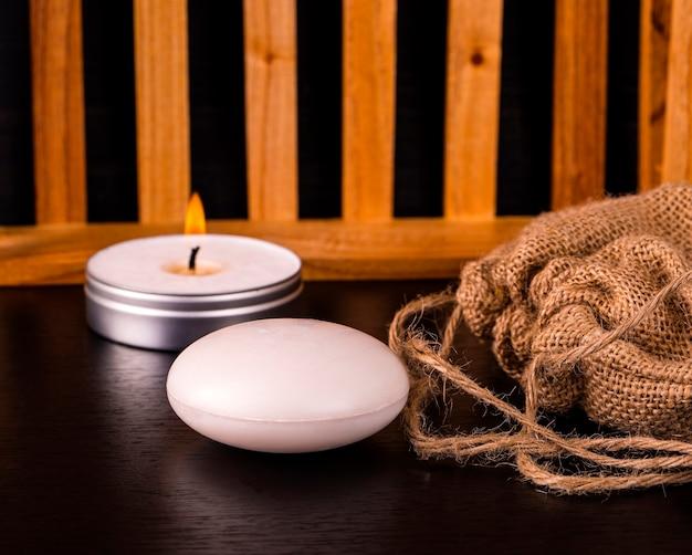 Composizione del trattamento termale su tavola di legno. sapone, candela e tela da imballaggio sul tavolo.