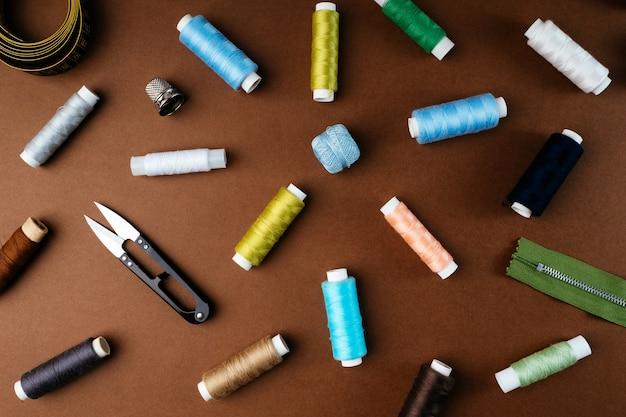 Composizione di bobine di filo e altri accessori per cucire su uno sfondo marrone, piatto piatto, vista dall'alto