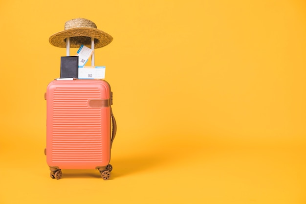 Composizione di valigia e biglietti passaporto e cappello su di esso