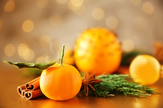 Composizione di mandarino, spezie e rami di conifere sul tavolo contro luci sfocate