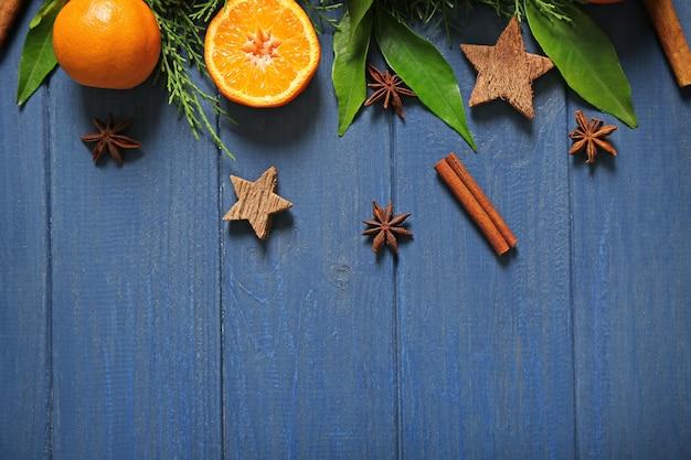 Composizione di mandarino, spezie e rami di conifere su tavola di legno
