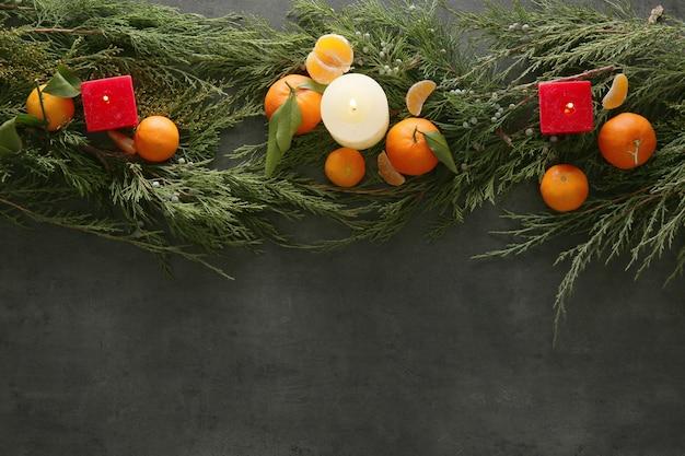Composizione di mandarini, candele e rami di conifere su superficie scura