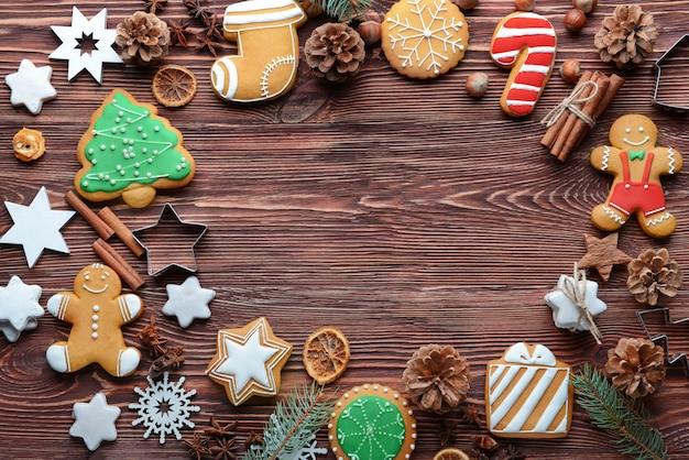 Composizione di gustosi biscotti e decorazioni natalizie su tavola di legno