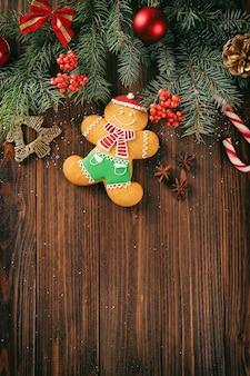 Composizione di gustoso biscotto di pan di zenzero e decorazioni natalizie su fondo di legno