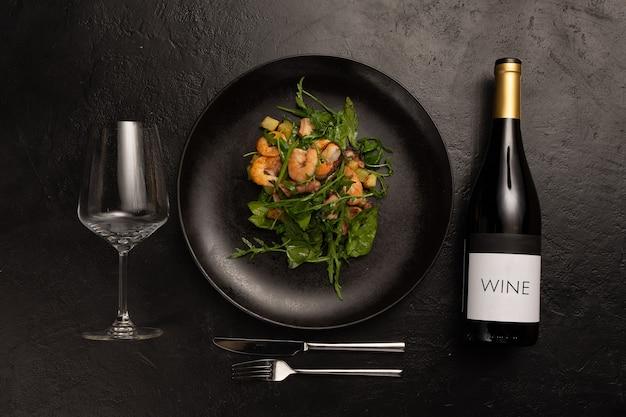 Composizione sul tema della decorazione del menù di un ristorante con antipasti di insalata, una bottiglia di vino, un bicchiere e posate su un tavolo di pietra nera.