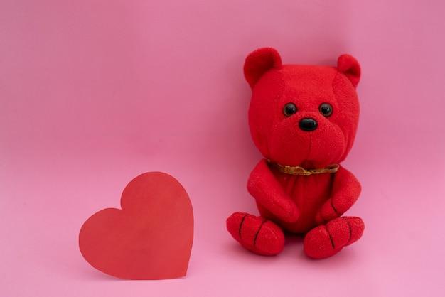 Composizione orso e cuore del giocattolo in rosso su una rosa