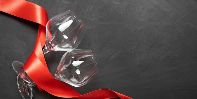Composizione due bicchieri di vino su uno sfondo scuro. nastro di raso rosso. concetto di vacanza per gli amanti. baner. copia spazio.