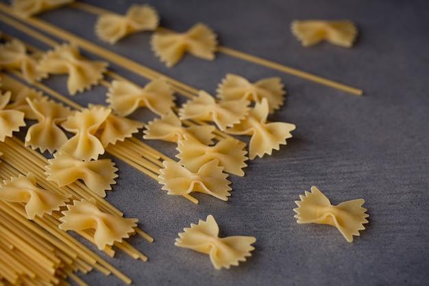 Composizione di pasta italiana cruda. spaghetti, farfalle, fusilli su fondo di legno scuro. sfondo di pasta cruda.