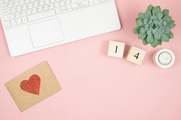 Composizione per san valentino febbraio. delicata superficie rosa, laptop e cosmetici. biglietto d'auguri. vista piana, vista dall'alto, copia spazio. Foto Premium