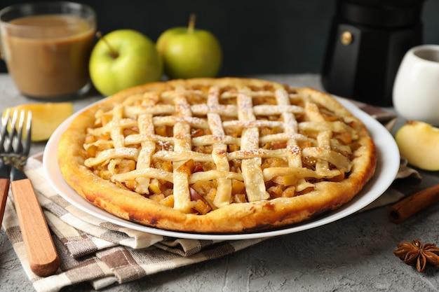 Composizione con torta di mele e ingredienti su sfondo grigio. cibo fatto in casa