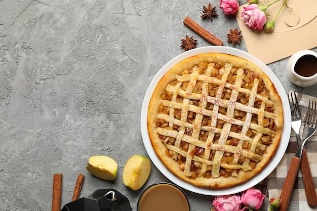 Composizione con la torta di mele e gli ingredienti su fondo grigio, vista superiore