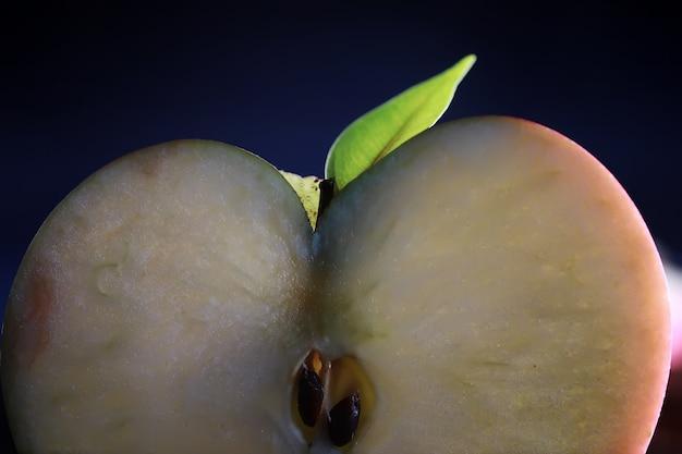 Composizione con fette di mela su sfondo nero. una fetta di mela con retroilluminazione su sfondo nero con gocce d'acqua. mela succosa su un tavolo.