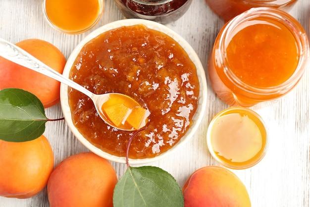 Composizione con marmellata di albicocche e frutta succosa matura sulla tavola di legno