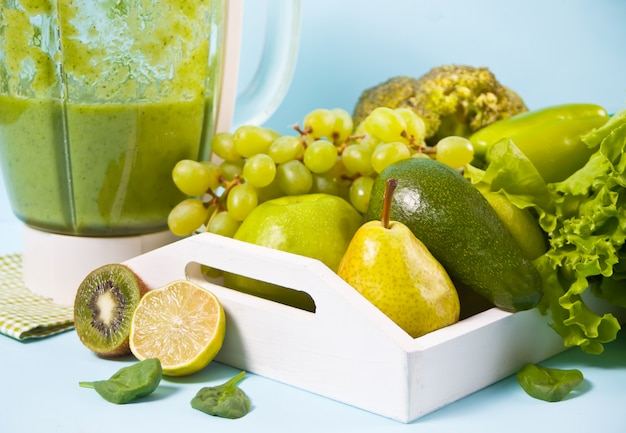 Composizione con verdure verdi organiche crude assortite e friuts sul vassoio in legno bianco e frullatore.