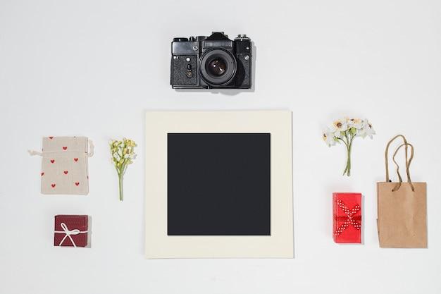 Composizione con cornice nera, retro macchina fotografica, scatole regalo rosse, borsa artigianale, borsa di tela con forme di cuore rosso e campo di fiori di primavera su sfondo bianco.