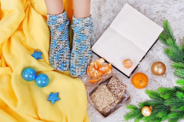Composizione con libro, gambe femminili e decorazioni natalizie su tappeto colorato