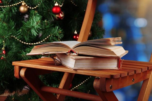 Composizione con libri sulla sedia sullo sfondo dell'albero di natale