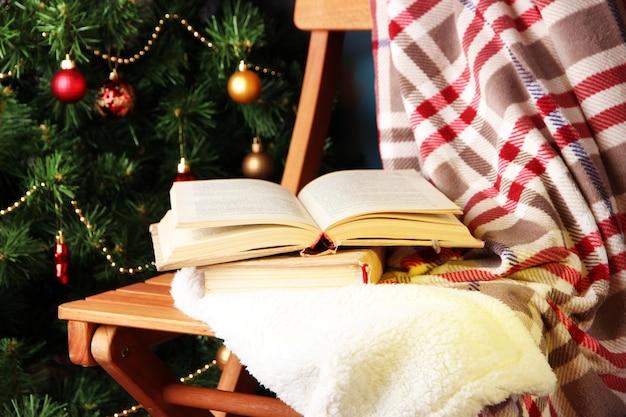 Composizione con libri e plaid su sedia sullo sfondo dell'albero di natale