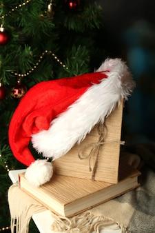 Composizione con libri e cappello rosso scozzese sulla sedia sullo sfondo dell'albero di natale