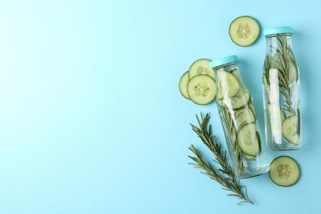 Composizione con bottiglie di acqua di cetriolo sulla superficie blu