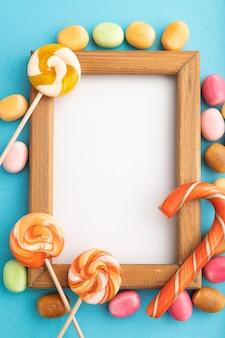 Composizione con caramelle e cornice in legno su pastello blu