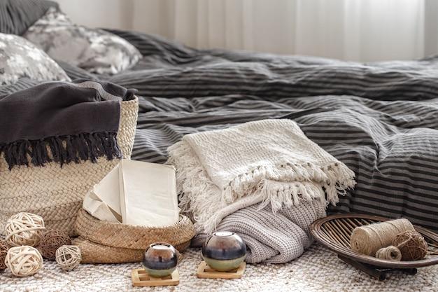 Composizione con candele, elementi in maglia e altri dettagli di arredo in camera da letto.