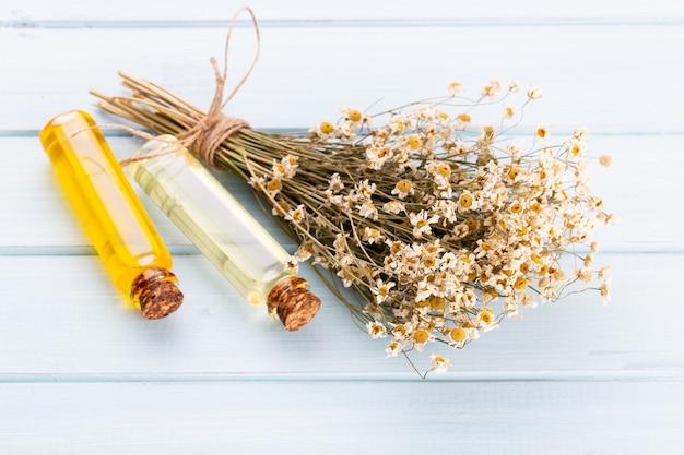Composizione con fiori di camomilla e cosmetici fatti in casa, olio essenziale, sopa, su sfondo bianco, vista dall'alto.