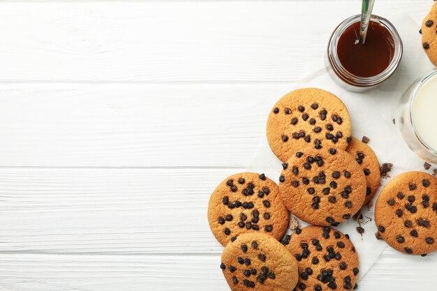 Composizione con biscotti, latte e caramello sul tavolo di legno bianco