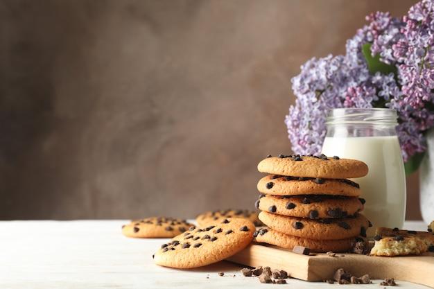 Composizione con biscotti al cioccolato, latte e lilla sulla tavola di legno bianca