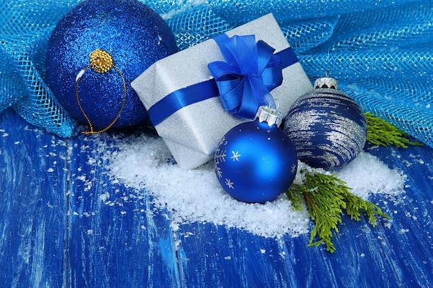 Composizione con palline di natale, confezione regalo e neve su fondo in legno colorato