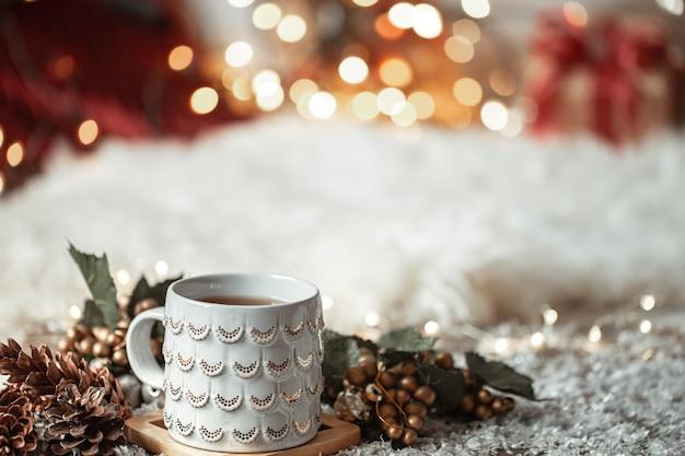 Composizione con tazza di natale con bevanda calda su sfondo sfocato astratto