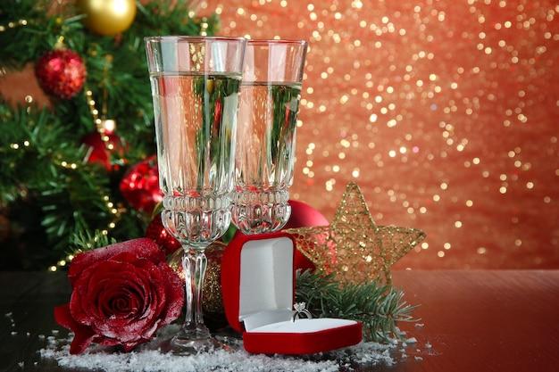 Composizione con decorazioni natalizie e due bicchieri di champagne, su sfondo luminoso