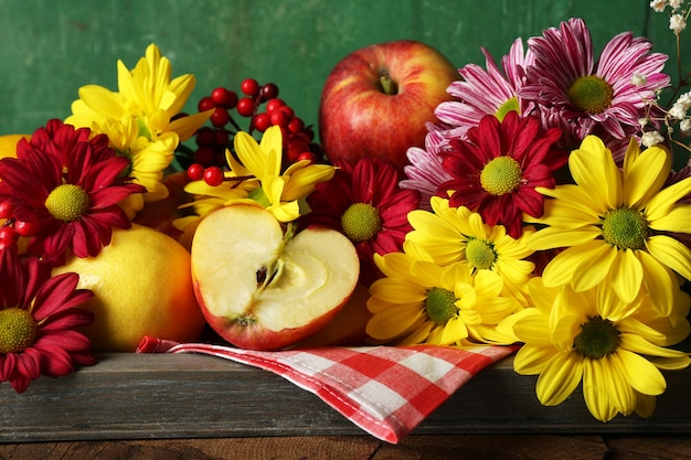 Composizione con crisantemo e frutta sulla tavola di legno